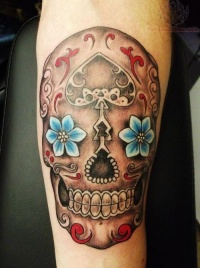 Awesome sugar skull with blue flower eyes tattoo