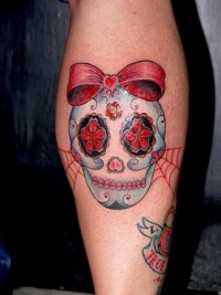 Cute sugar skull with a red bow tattoo