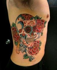 Sugar skull with roses tattoo on ribs